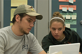 Male and female student looking at a computer