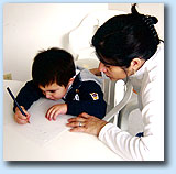 Action shot of a female teacher instructing a young student in writing.