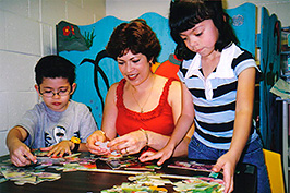 woman plays with puzzle with kids