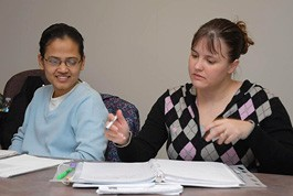 two female students review notes in class