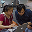 Two Chinese graduate students, Huihui Zhang (left) and Tian Fu, look over a document on a laptop